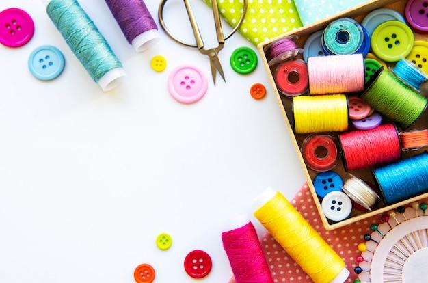 白い背景にアクセサリーや生地を縫う。ミシン糸、針、ピン、生地、ボタン、ミシンセンチ。上面図、フラットレイ。