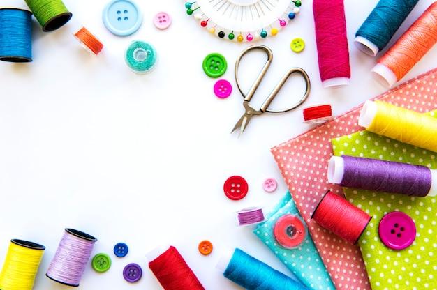Швейная фурнитура и ткань на белой поверхности. швейные нитки, иглы, булавки, ткань, пуговицы и швейный сантиметр. вид сверху, плоская планировка.