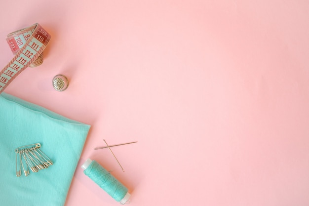 Sewing accessories, turquoise fabric on pink background. fabric, pins, threads and needles.