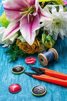 Sewing accessories with a bouquet of fresh flowers on turquoise background