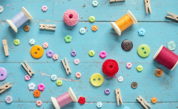 Sewing background. accessories for needlework on old wooden background.