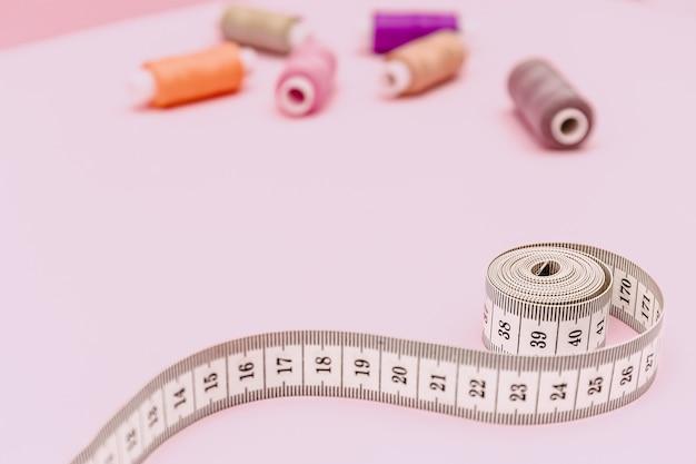 Фон шитья с рулеткой на розовом фоне. аксессуары портного или швеи. швейные нитки, иглы, ткань, швейный сантиметр или рулетка.