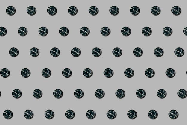 Швейные пуговицы узор на сером фоне в стиле плоской планировки. концепция моды, дизайна, презентации, баннеров или интернета. вид сверху. крупный план