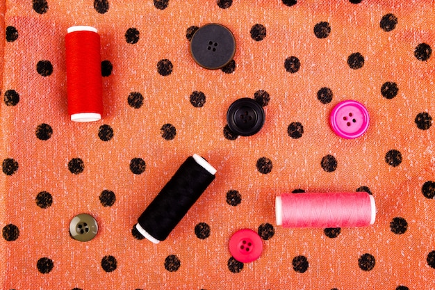 Sewing buttons, spools of thread and cloth on wooden table