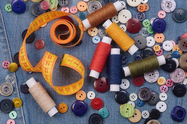Sewing buttons, yellow measuring tape and thread spools.