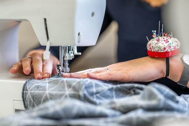 仕立て屋のミシンで布を縫う。