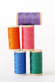 Cucire. fili colorati su una superficie bianca