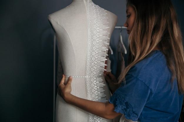 縫製のコンセプトです。テーラーショップでダミーを測定する若い白人女性。作業コンセプトを調整します。趣味のコンセプトです。