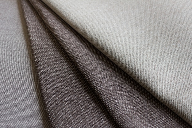 Sewing hand making composition with folded layers of dark brown textured fabric.