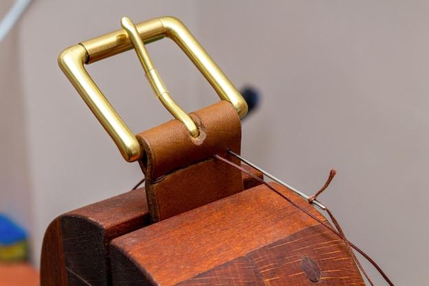 Пошив ручной работы из коричневого кожаного ремня процесс