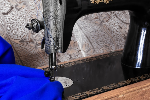 Sewing head of antique sewing machine with presser foot during hemming bright blue fabric close up