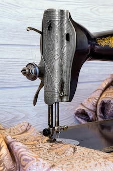 Sewing head of antique sewing machine with presser foot during hemming close up, vertical frame