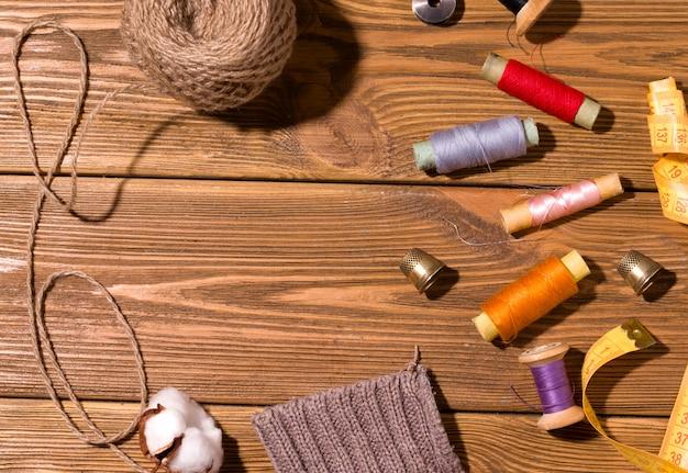 自宅での趣味のコンセプトを縫製。スレッドと木製スペースのボタン。コピースペース。