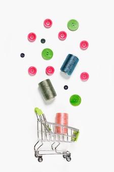 Швейные изделия сверху плоской композиции со швейной фурнитурой на светлом фоне