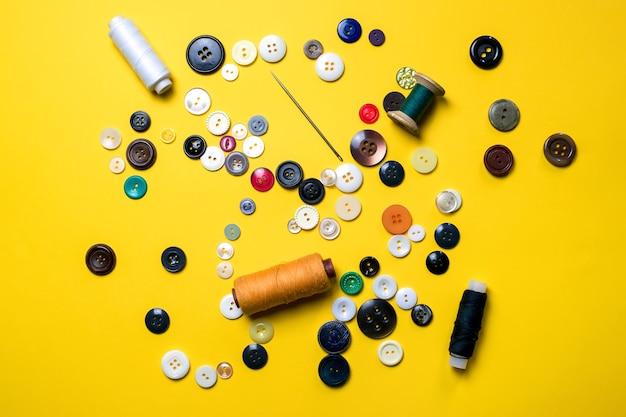 Набор для шитья. лежат разноцветные пластиковые пуговицы, катушки с нитками и швейные иглы.