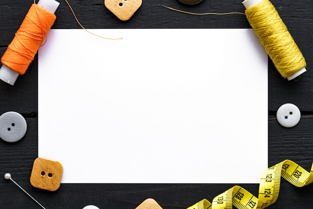 Sewing kit and various sewing accessories for tailoring for seamstress on dark wooden background top view. copy space