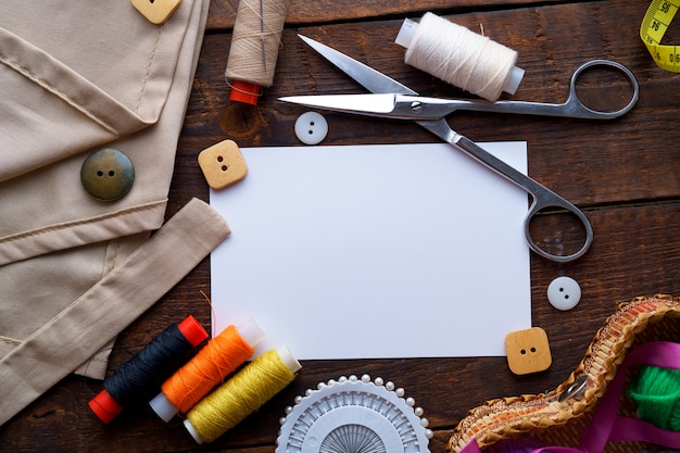 Sewing kit and various sewing supplies for needlework for seamstress on dark wooden background