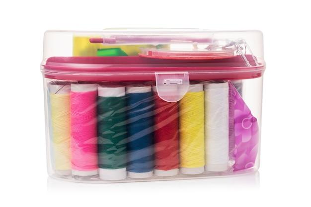 Швейный набор с разными катушками ниток в прозрачной пластиковой коробке на белом фоне