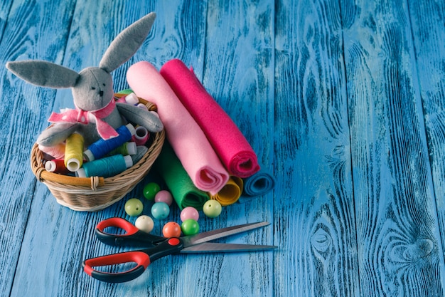 Sewing kit on a wooden table. thread, needles, scissors and a toy on the table.