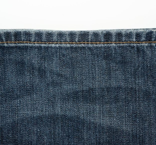 Sewing line from brown threads on blue jeans, close-up
