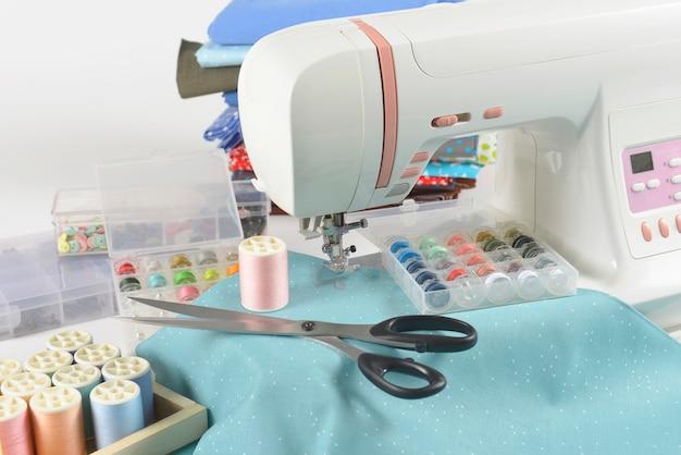 Швейная машина и красочные рулоны, ножницы, ткани и аксессуары для шитья.