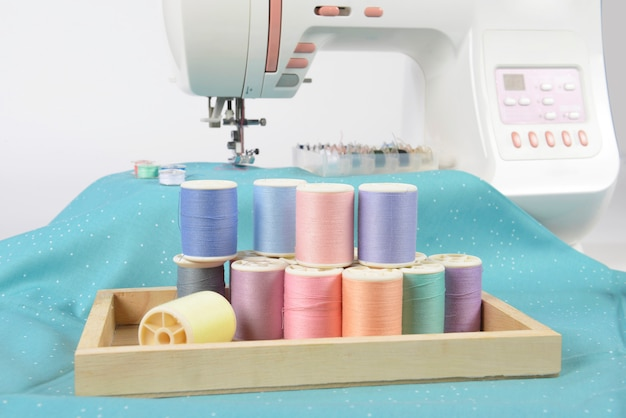 Sewing machine and colorful thread rolls, scissors, fabric and accessories for sewing.