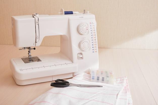 Швейная машина, ткань, ножницы и катушки ниток на столе