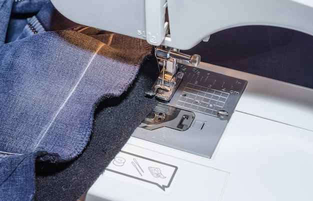 Sewing machine foot on denim fabric overcasting process