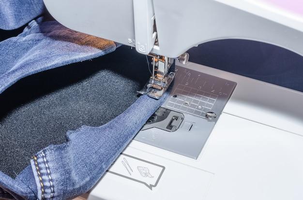 Sewing machine foot on denim, hem hemming