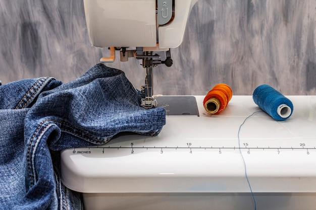 Sewing machine foot on denim. scissors, spools of thread. stands on a table