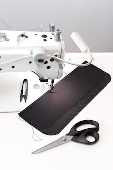 縫い目の白いテーブルの上のミシン。閉じる