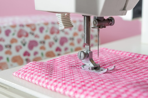 Sewing machine, pink fabric needle close-up with selective focus on a light background with copy space