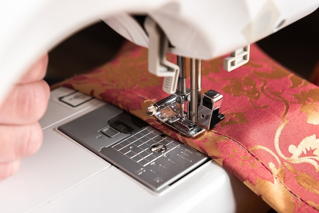 The sewing machine's foot with a needle sews red fabric with flowers.