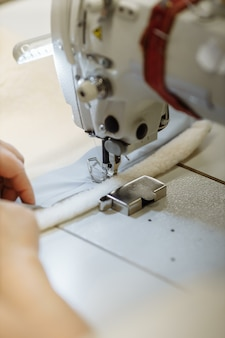 Швейная машина строчит пошив ткани на фабрике