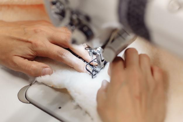 Швейная машина строчит ткань. пошив одежды на фабрике.