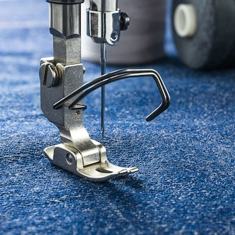 Sewing machine and threads parts as follows presser foot on denim blue fabric