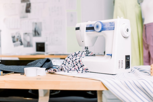 Sewing machine with fabric on table in tailor workshop. professional sewing machine on the background of atelier studio. sewing machine, rolls of thread, fabric, scissors. sewing business concept.