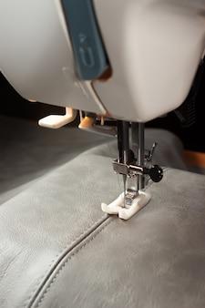 특수 노루발이있는 재봉틀은 회색 가죽에 솔기를 만듭니다. 바느질 과정을 닫습니다.