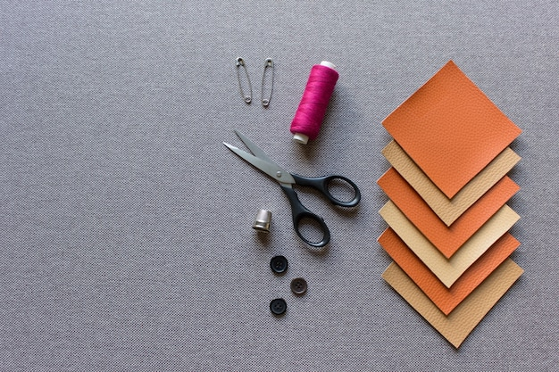 Sewing mockup template with fabric artificial leather squares, scissors, pin, threads and buttons