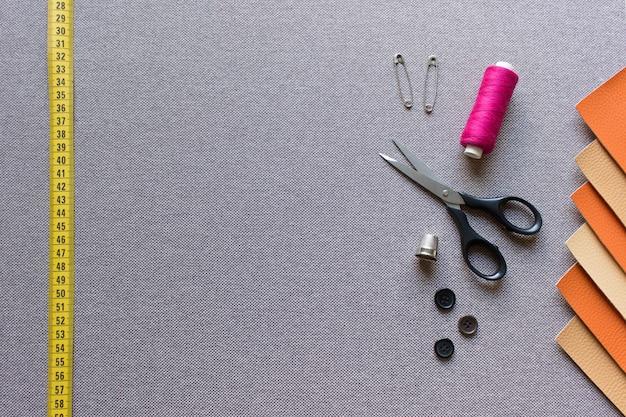 Шаблон швейного макета с желтой рулеткой, квадратики из искусственной кожи, ножницы, булавки, нитки и пуговицы