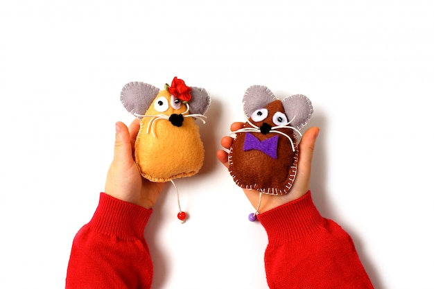 Sewing mouse toys from felt on children's hands.
