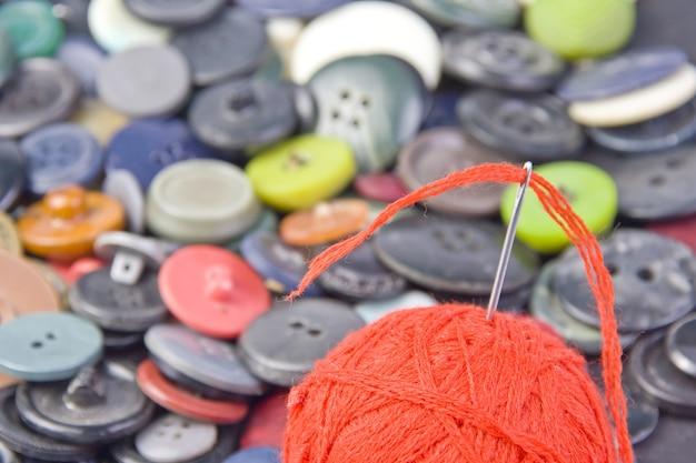 단추와 스레드의 공에 바느질 바늘