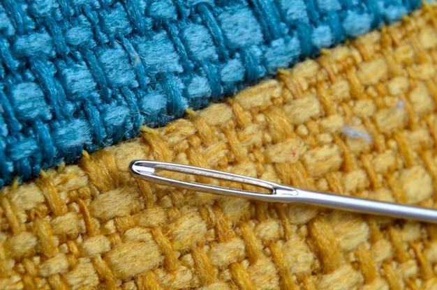 黄色の生地の背景に針を縫います。閉じる。
