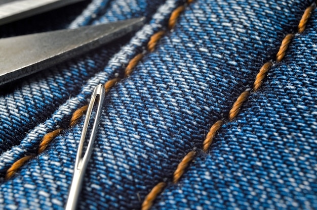 Sewing needle and scissors lie on blue jeans. close-up.