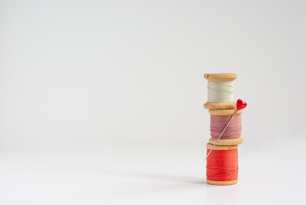 Sewing needle with red heart at the end and three vintage wooden spools of thread