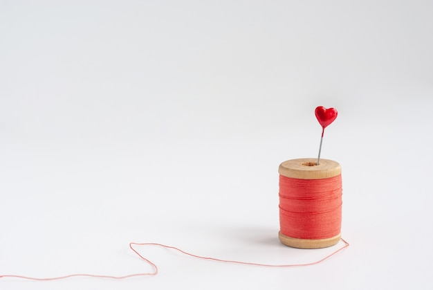Sewing needle with red heart at the end and vintage wooden spool of thread