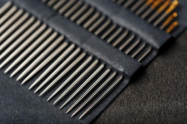 Швейные иглы на черном фоне в ряд.
