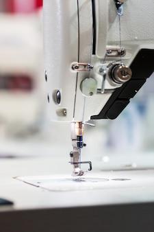 Швейная машина или оверлок крупным планом, никто. заводское производство, швейное производство