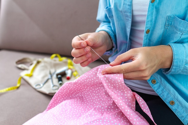 Sewing process. housewife patches clothes and sews at home using needle and various sewing supplies