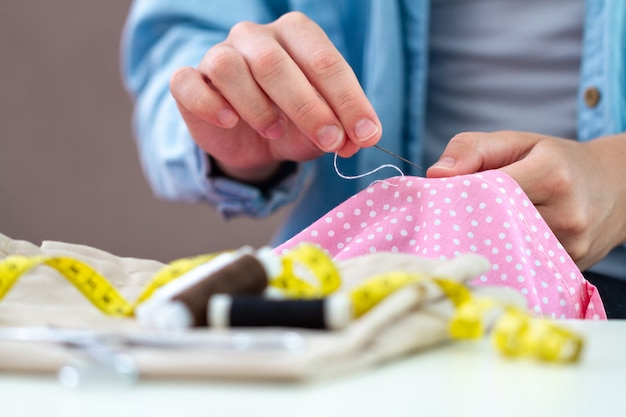 Sewing process. housewife sews at home using needle and various sewing accessories